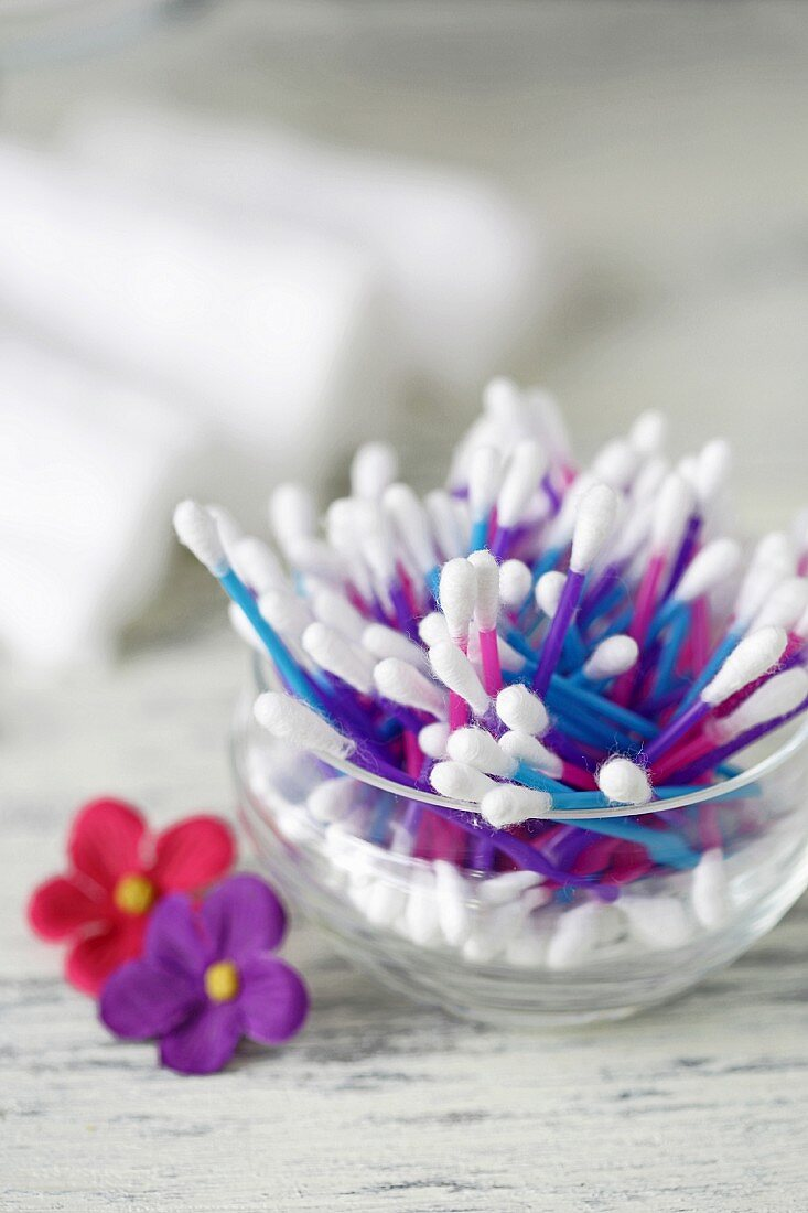 Colourful cotton buds in a jar next to fabric flowers