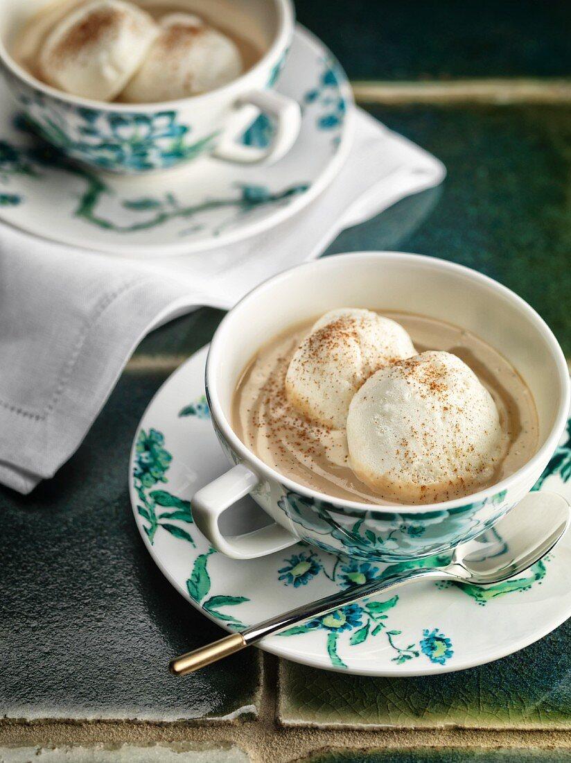 Egg white dumplings in tea and vanilla cream with ground cinnamon