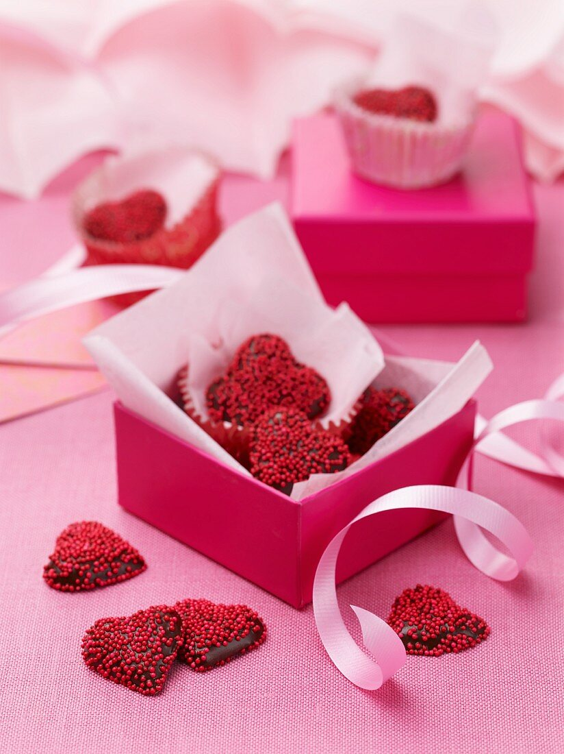 Dark chocolate hearts decorated with red sugar sprinkles as a gift