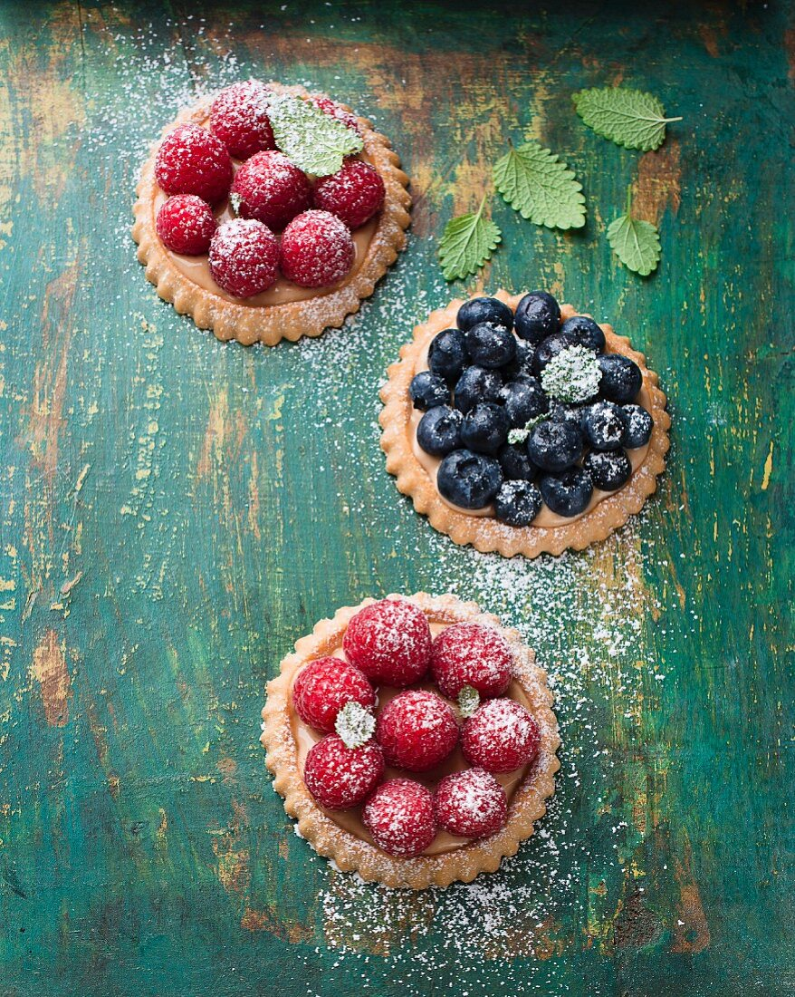 Raspberry tartlets and blueberry tartlets with icing sugar
