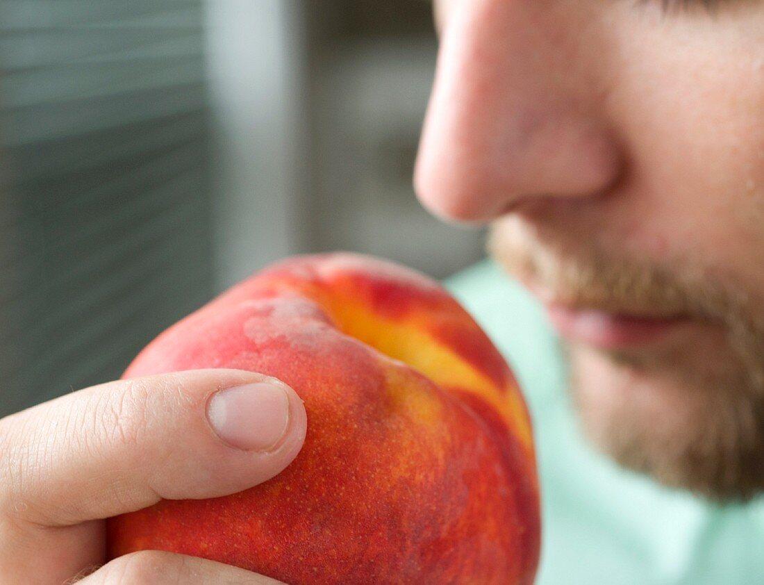A man sniffing a peach