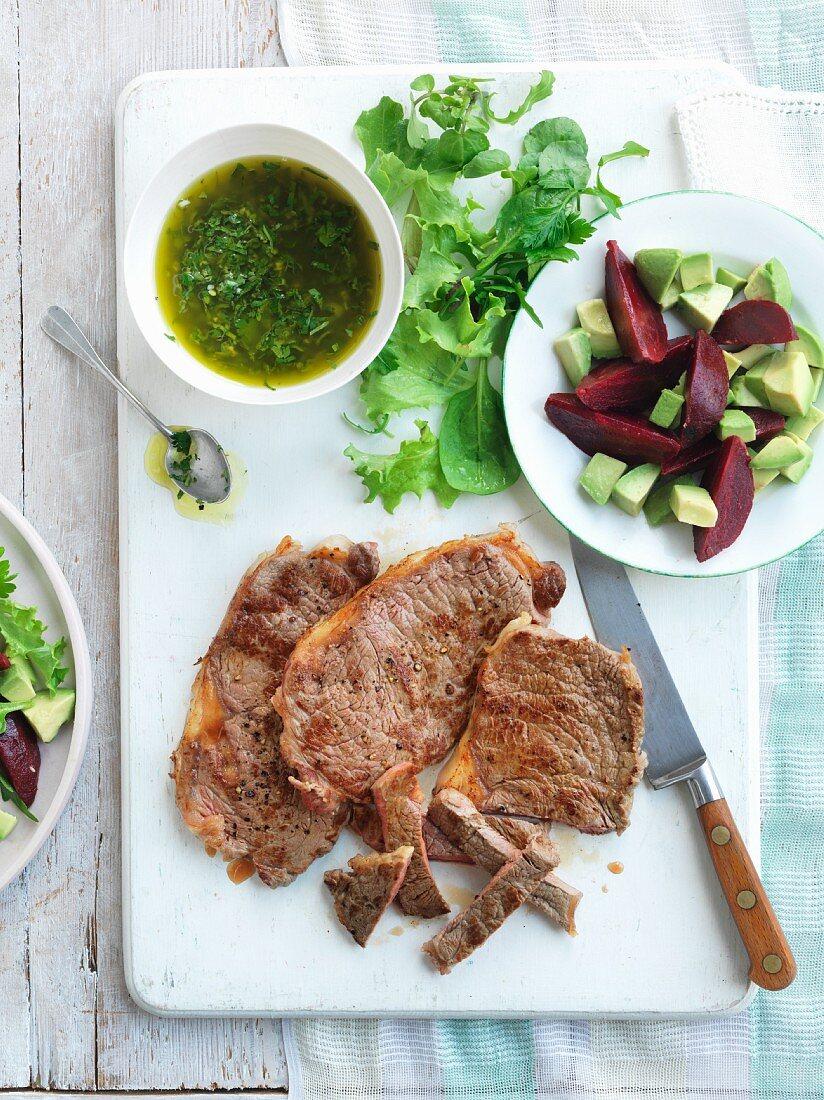 Beef steaks with salad and chimi-churri sauce