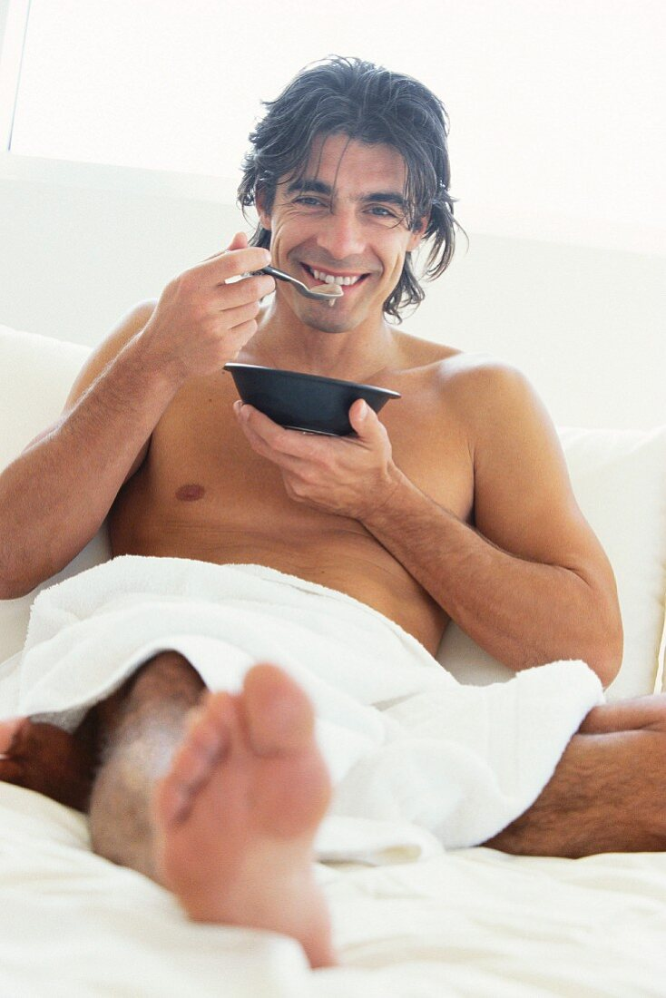A man eating muesli in bed