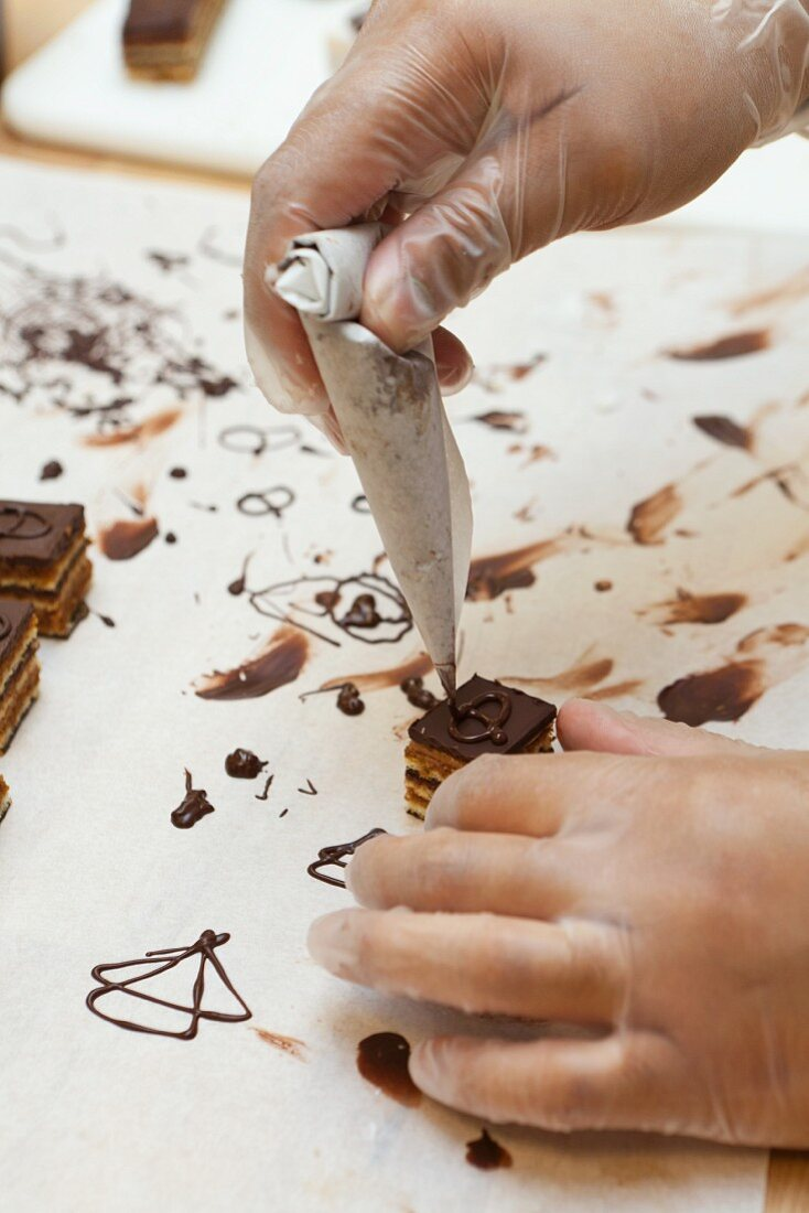 A confectioner decorating a petit four with chocolate