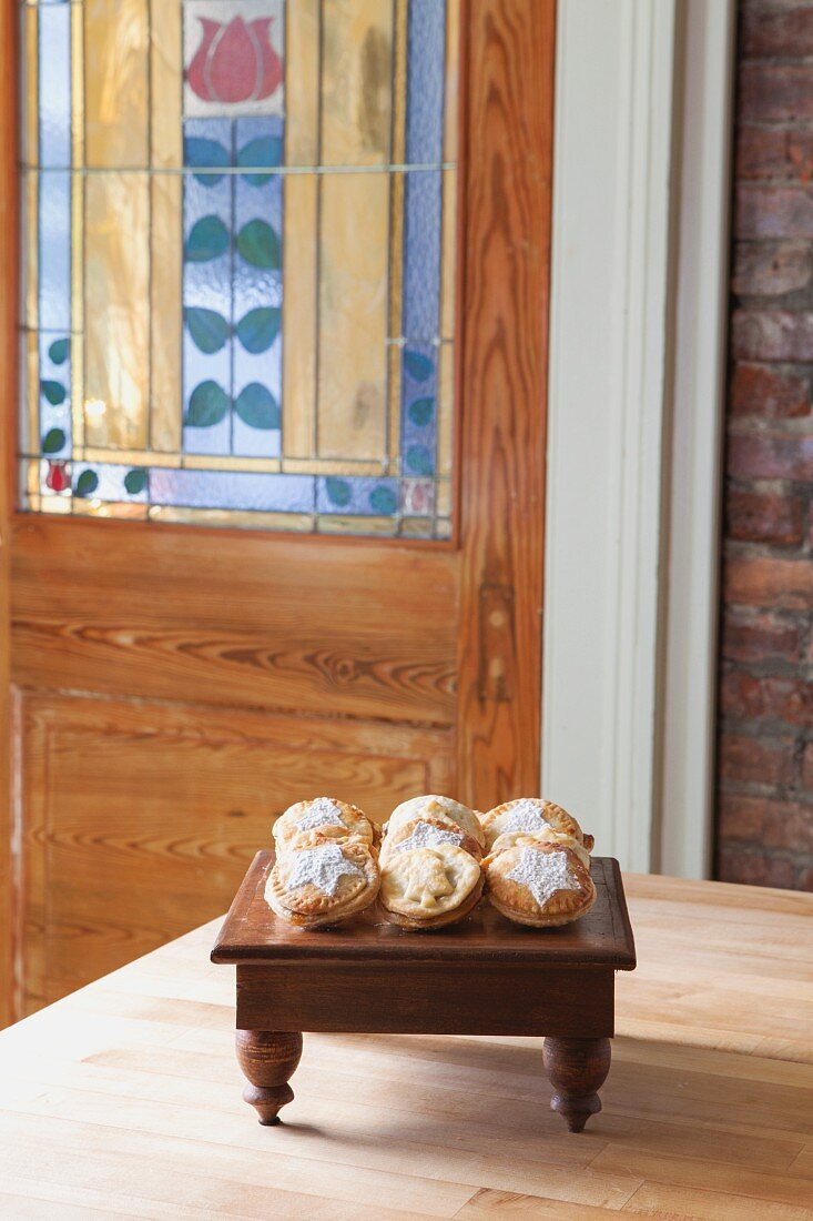 Rows of mince pies on a small wooden table in a living room