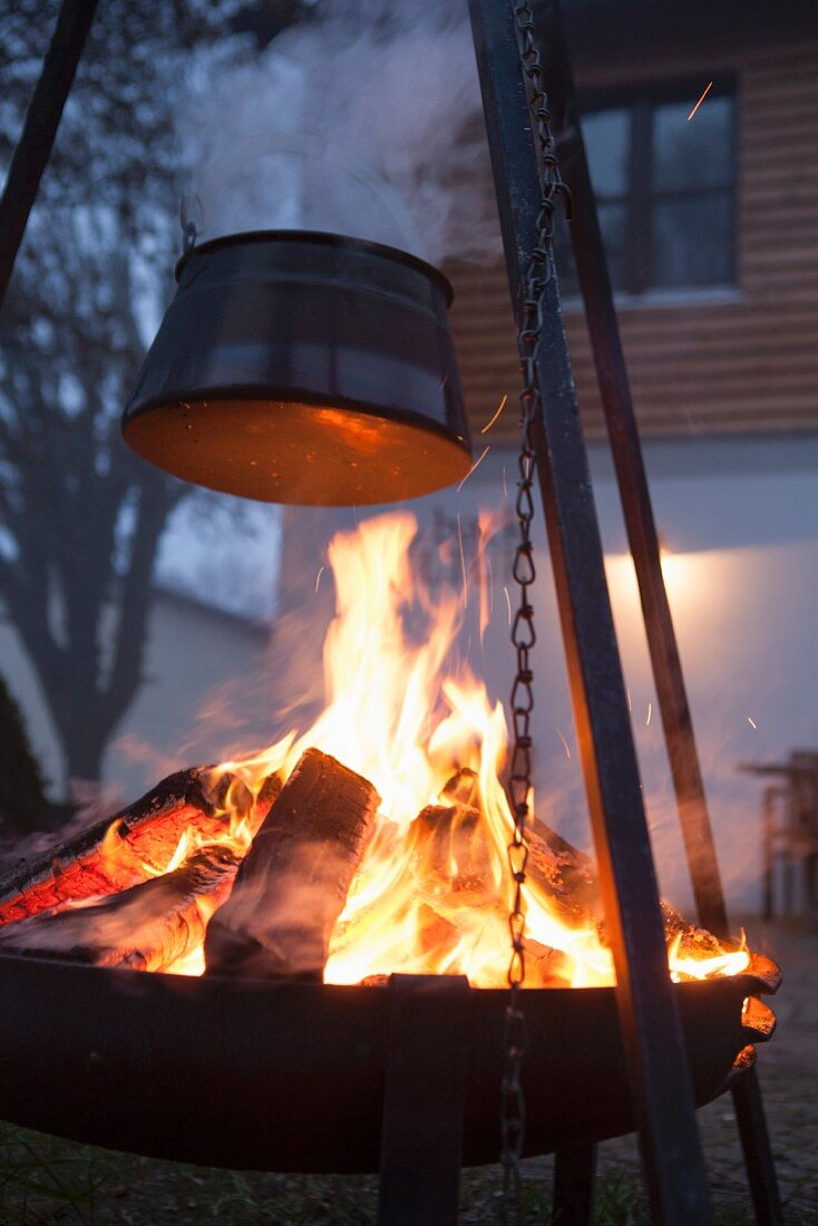 Metal tripod and cauldron over fire in brazier at twilight