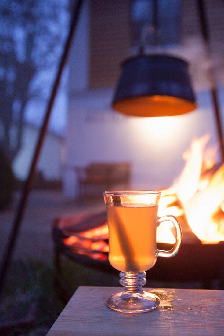 Hot drink in glass mug in front of fire in brazier in garden