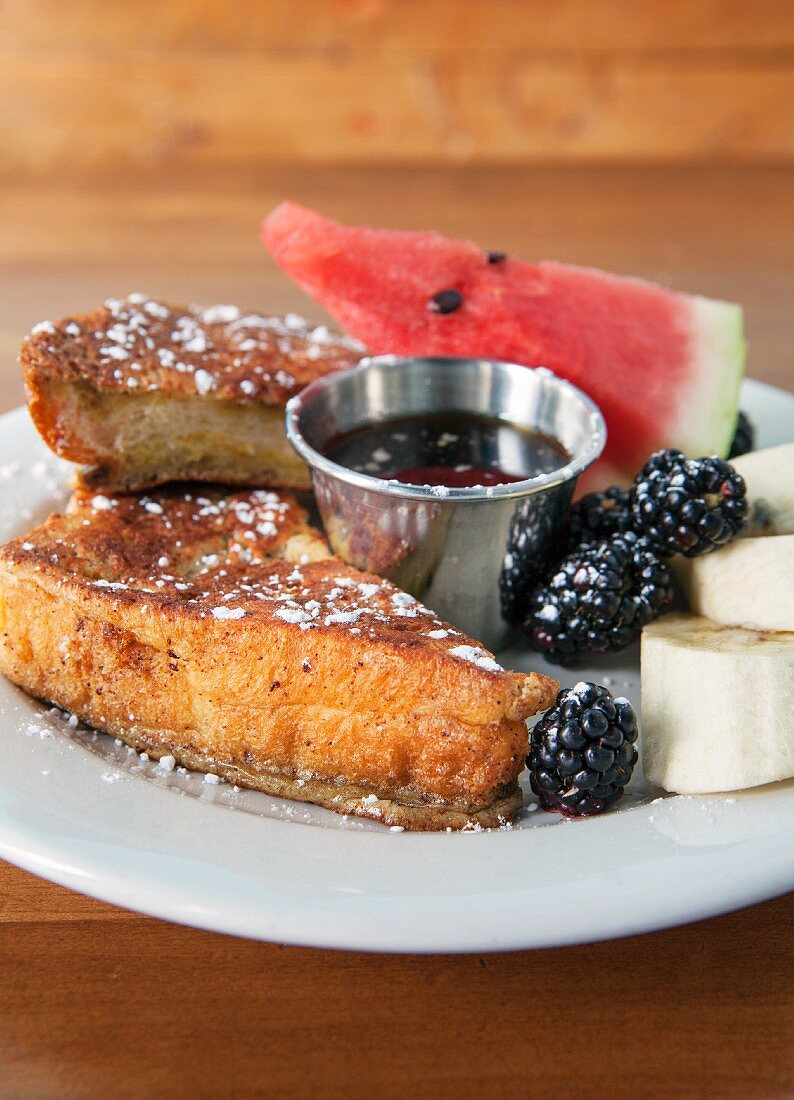 French toast with blackberries, bananas, watermelon, maple syrup and icing sugar