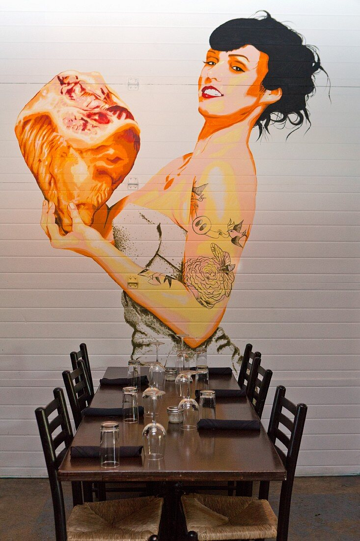 A pin-up style mural on a wall in a restaurant