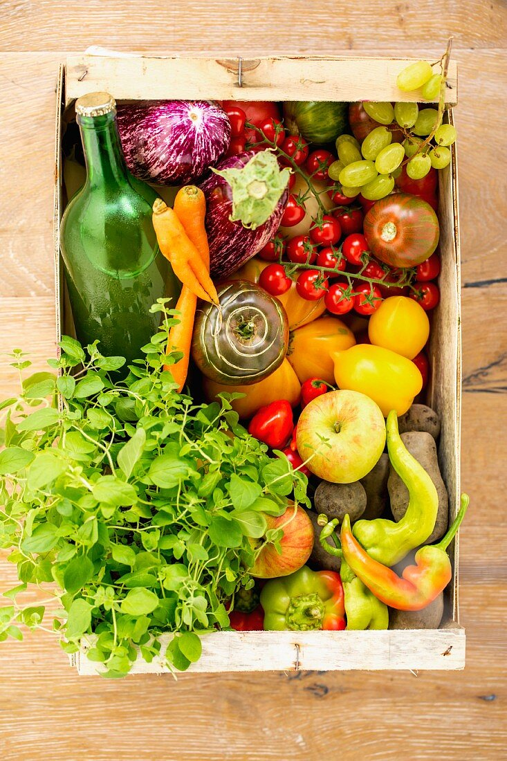 Fruit, vegetables, apple juice and herbs in a crate