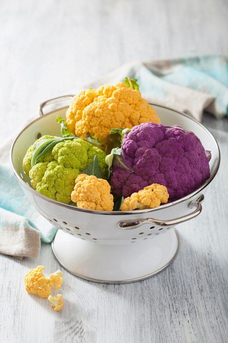 Different coloured cauliflower in a colander