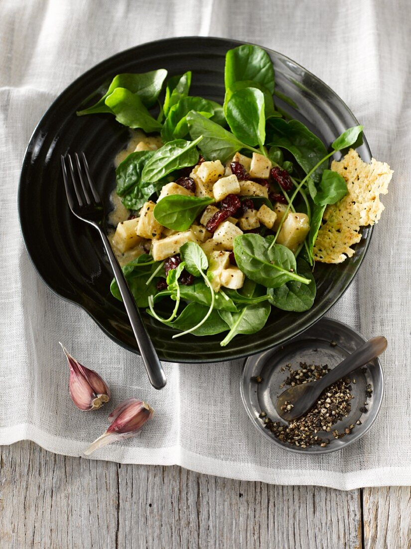 A winter salad with celeriac, spinach, dried cranberries, Parmesan crisps and a Dijon mustard dressing
