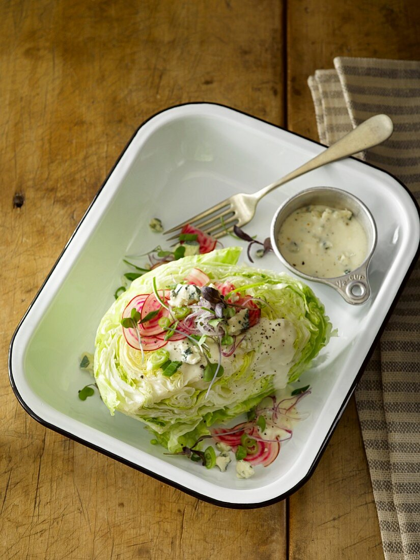 Iceberg lettuce with radish slices, red onion, cress and a blue cheese dressing