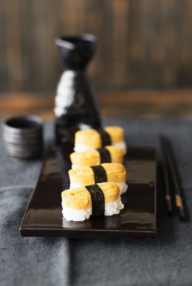 Tamago nigiri sushi on a black varnished platter