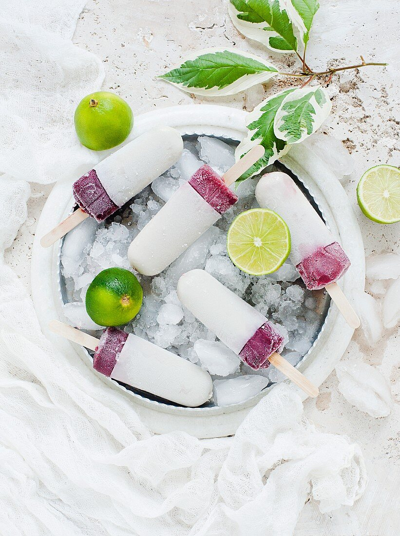 Fruit ice lollies dipped in yoghurt in a bowl of ice cubes