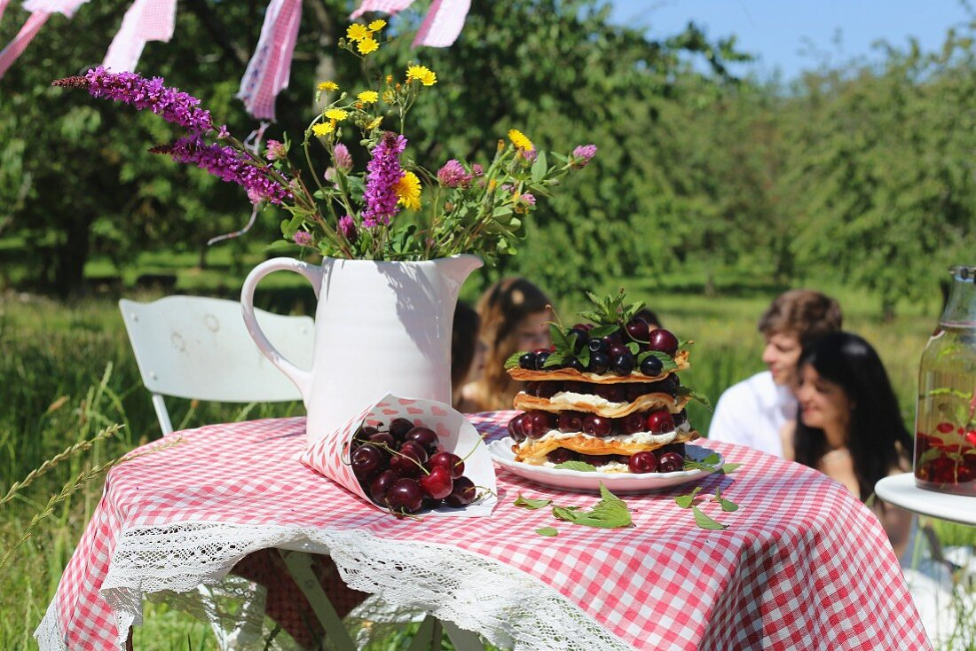 Fresh cherries, a stack of waffles and a jug of wild flowers on a garden table with a checked tablecloth with people in the background