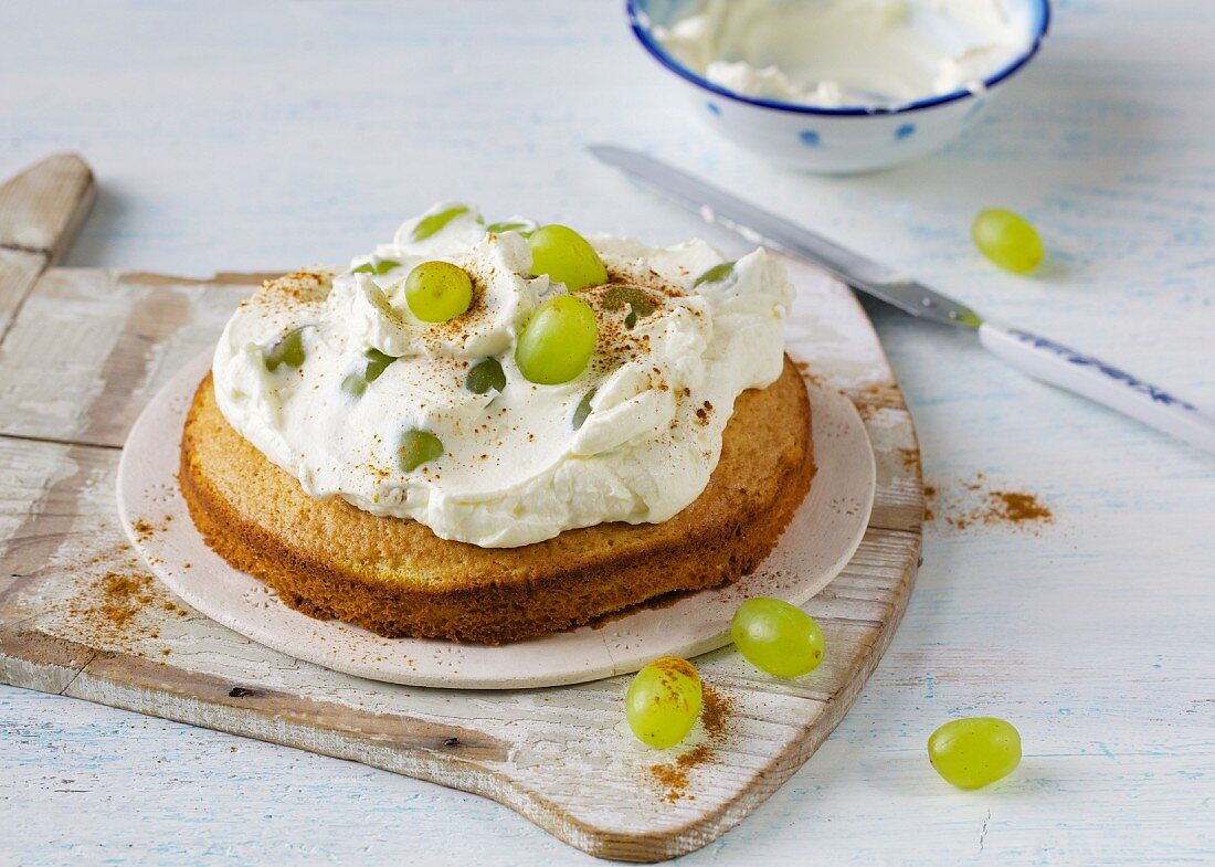 A mini sour cream cake topped with grapes