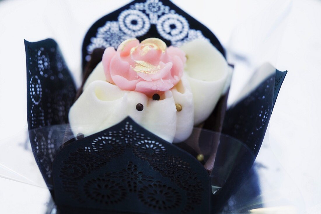 An elegant praline decorated with a rose in a black paper case