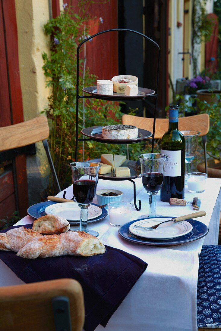 A table laid with red wine, baguette and a stand of cheese on a terrace