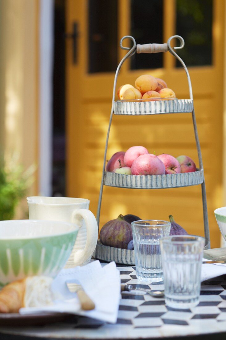 Figs, apples and apricots on a vintage stand on a breakfast table in a garden