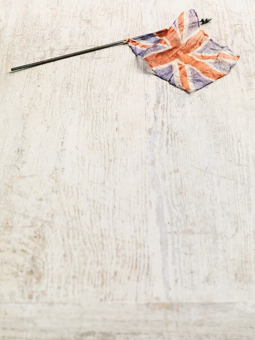 A British flag on a white wooden surface