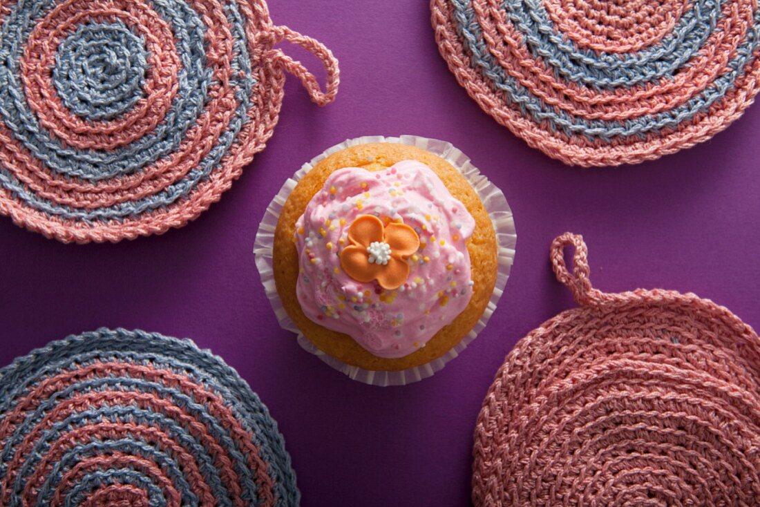 A flower cupcake between crocheted pot holders