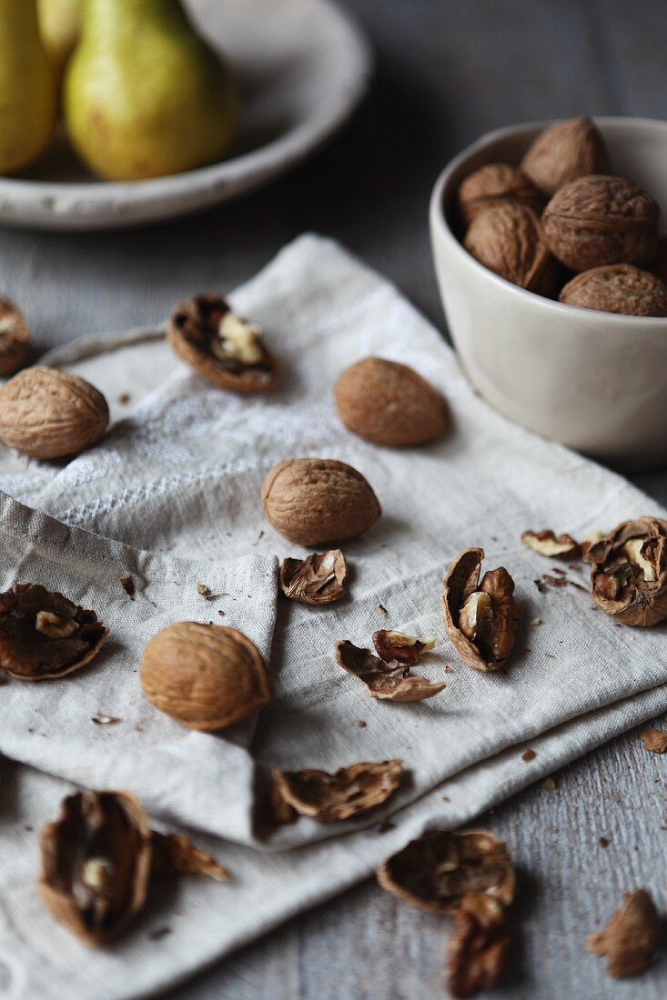 Walnuts and walnut shells on a cloth with a plate of pears in the background