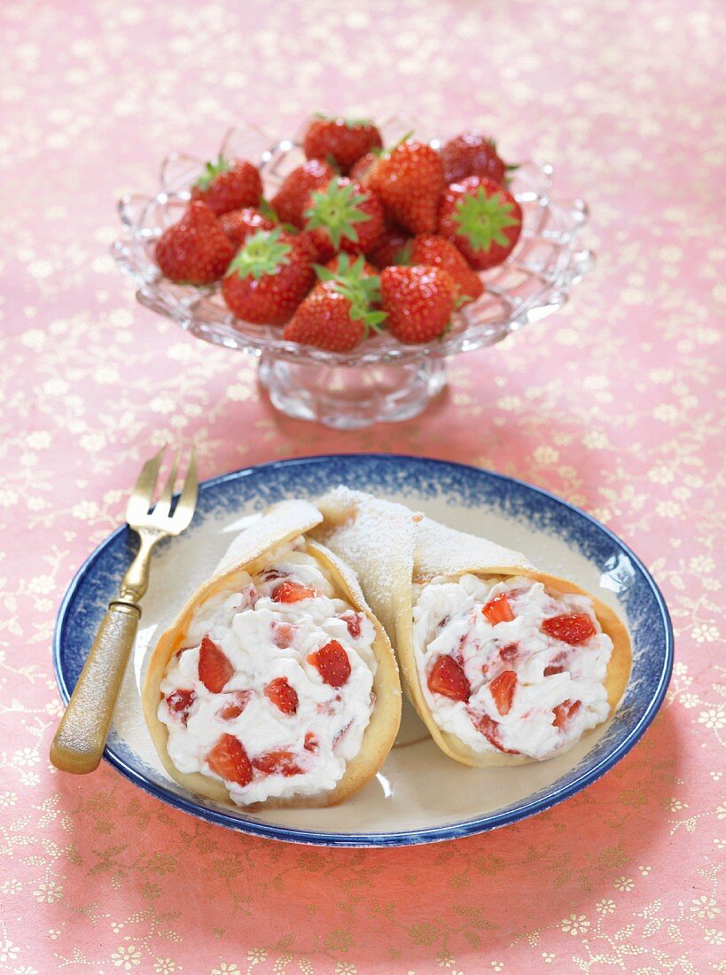 Wafer cones filled with cream and strawberries with icing sugar