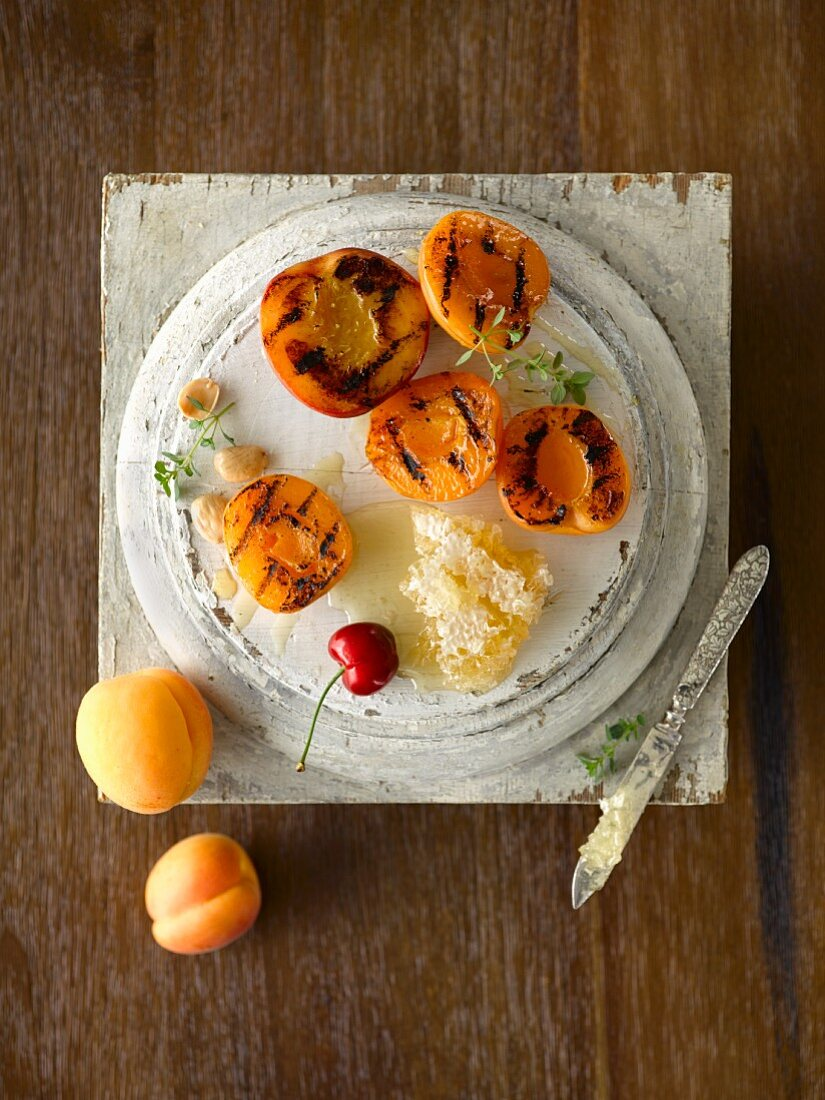 Grilled peach and apricot halves with honeycomb