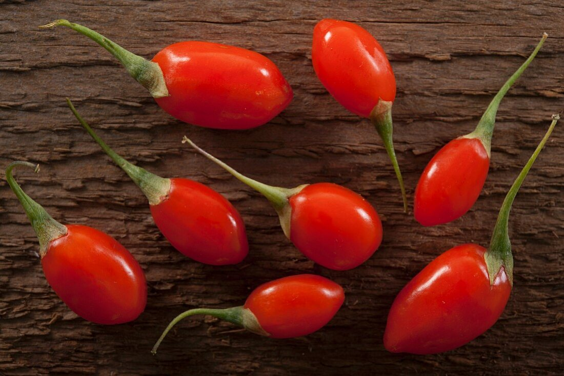 Bright red goji berries on a rustic wooden surface