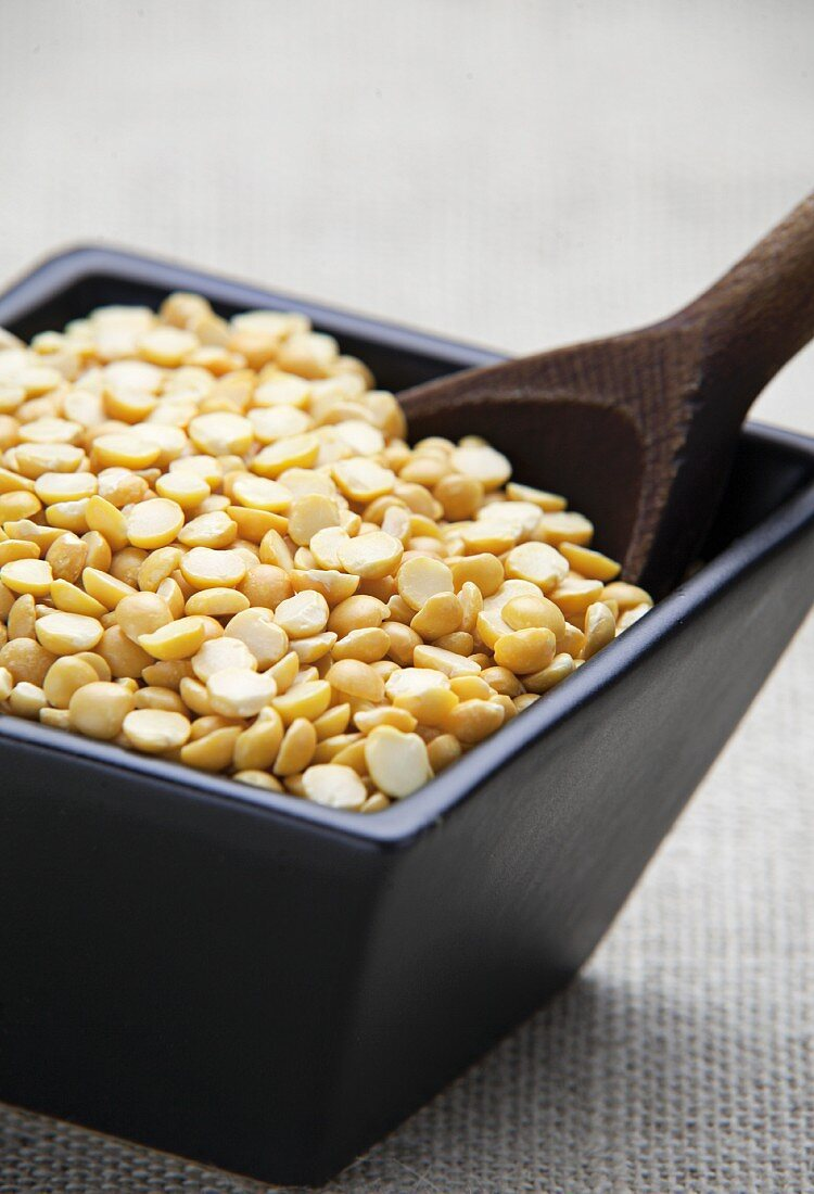 Dried yellow split peas in a bowl with a wooden spoon