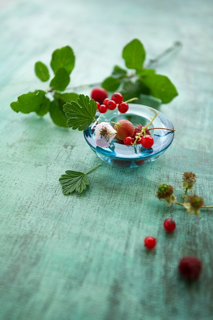 Various berries with leaves in a glass bowl