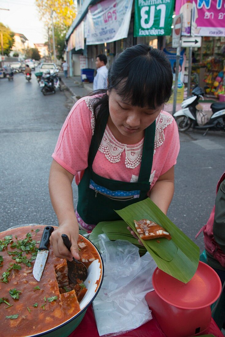 A woman selling Northern Pork Curry, Thailand
