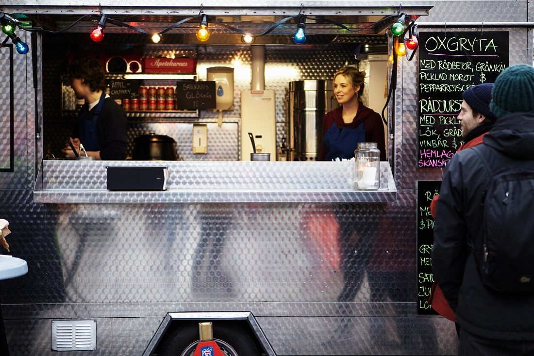 Men in front of the mobile food unit with a sales couple behind the counter