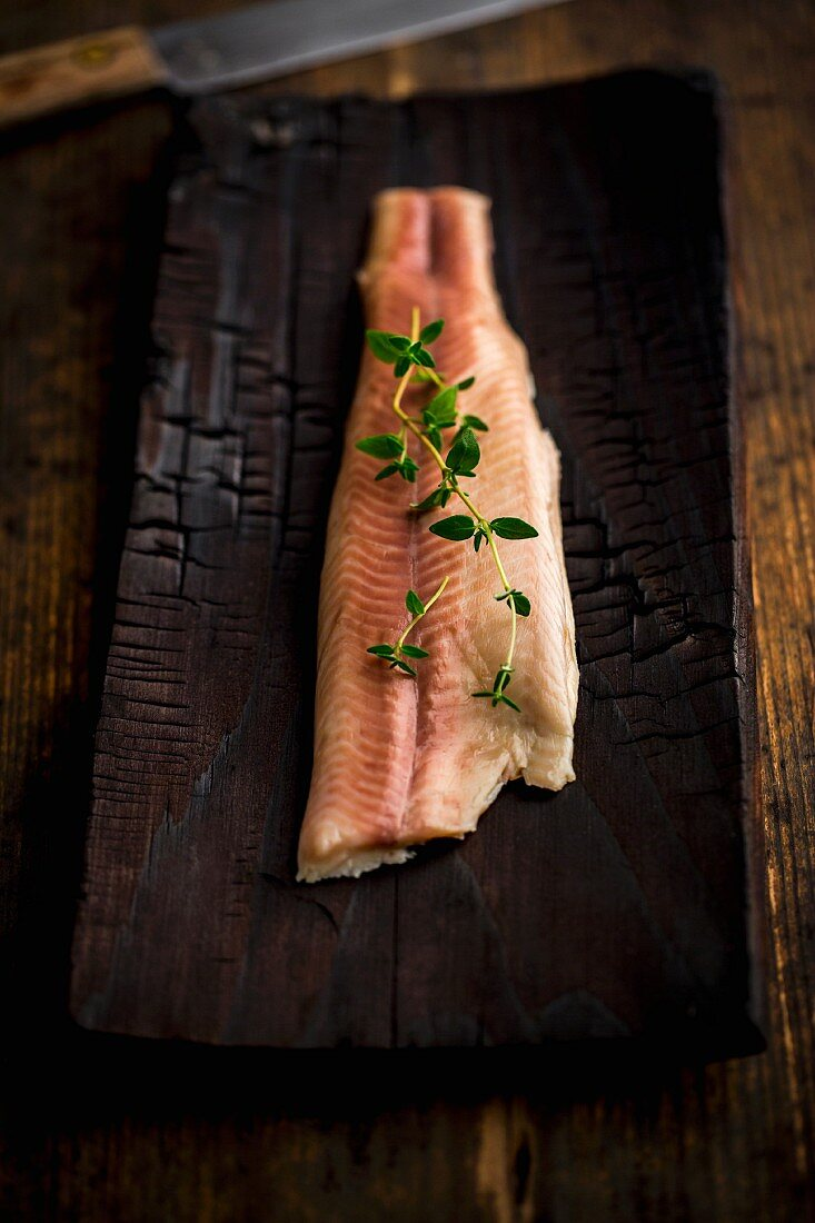 Smoked char on a wooden plank