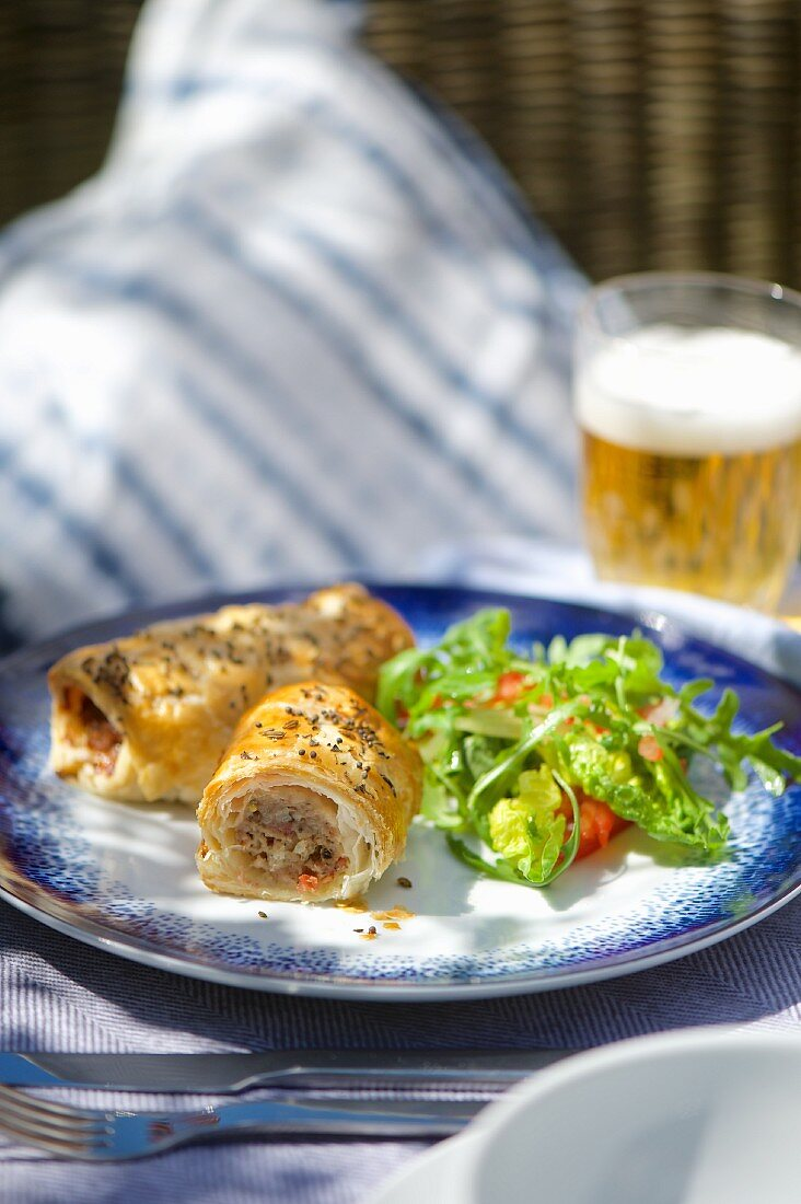 Sausage rolls with salad and a beer