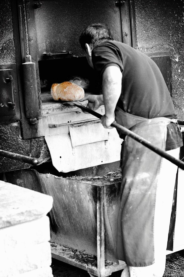 A baker removing a golden brown loaf from the oven