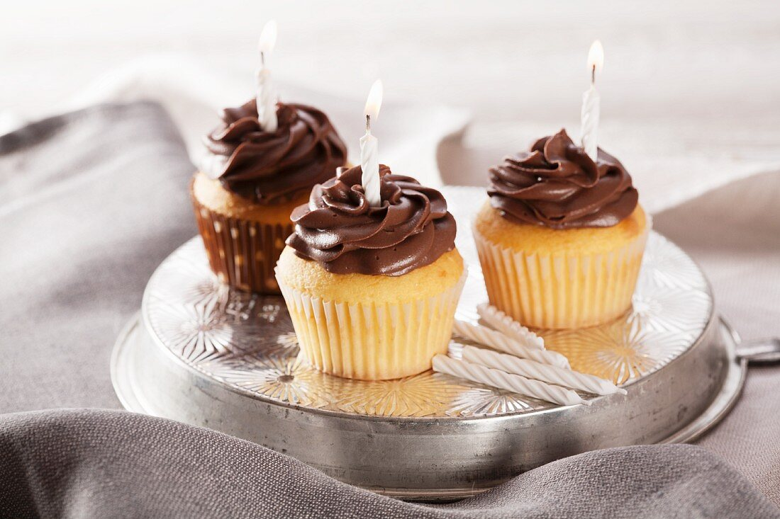 Three birthday cupcakes with lighted candles
