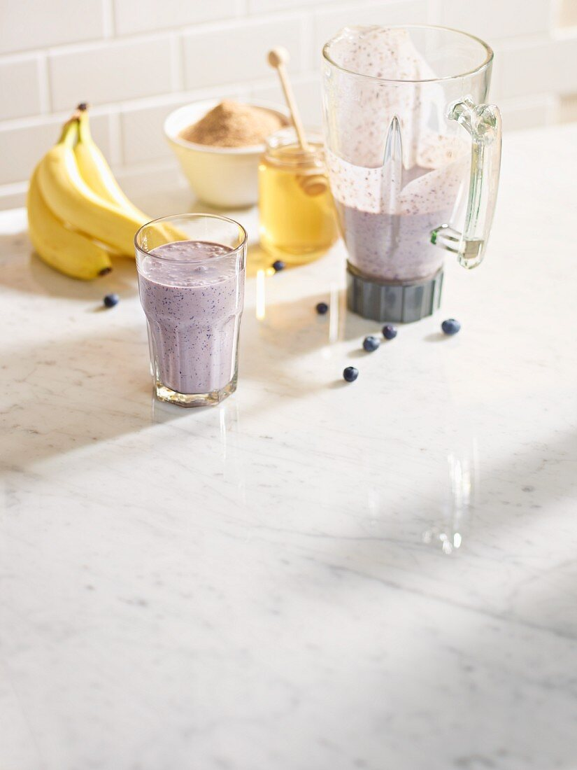 Blueberry and banana smoothie in a blender jug and in a glass with sugar and family
