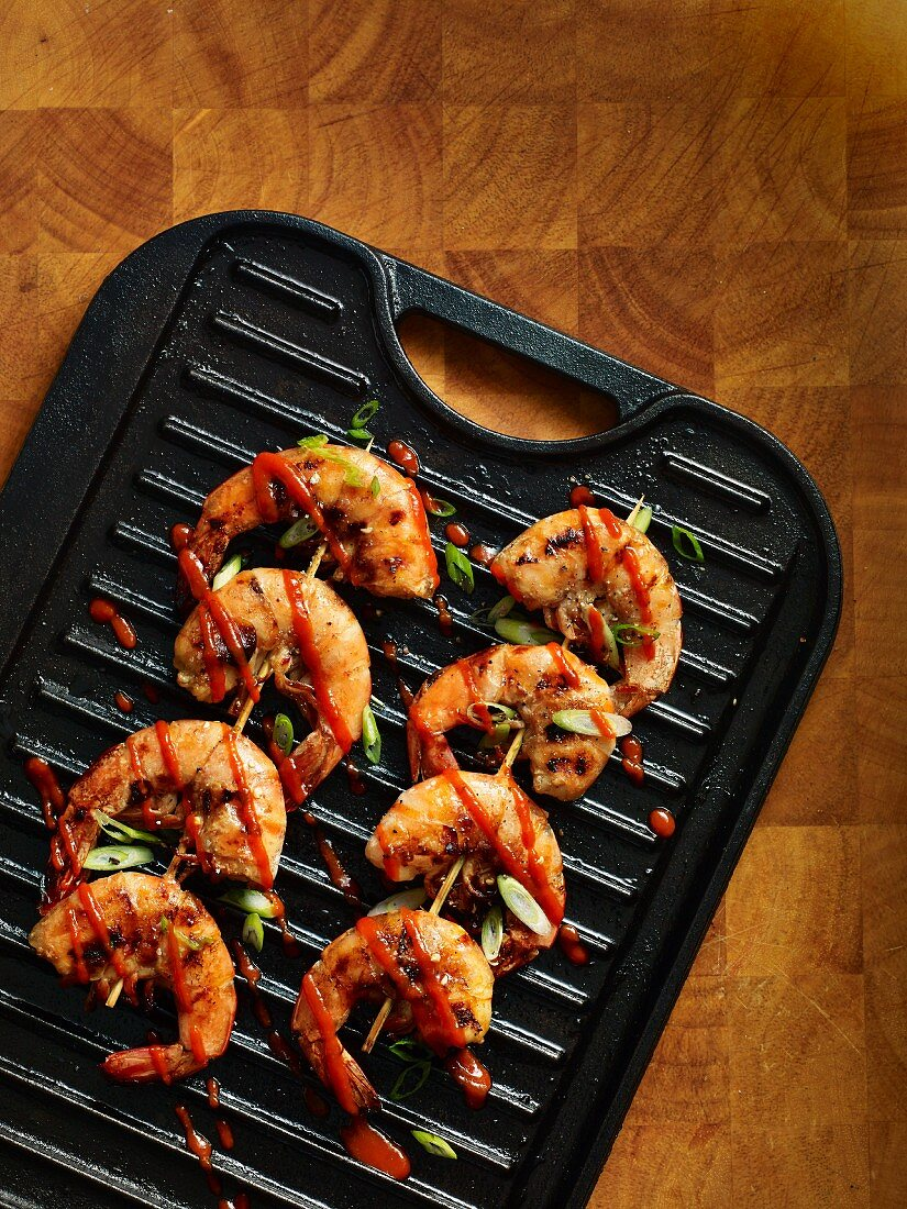 Grilled prawn skewers on a grill pan (seen from above)