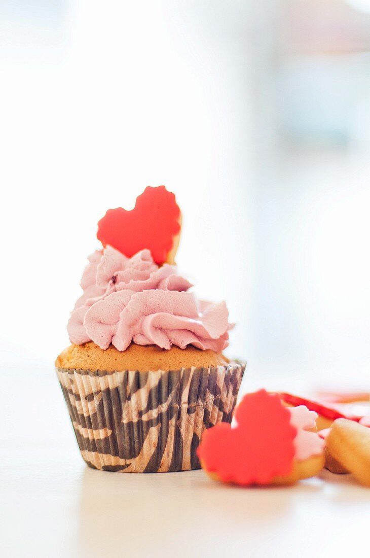 A cupcake topped with pink buttercream and a heart-shaped biscuit