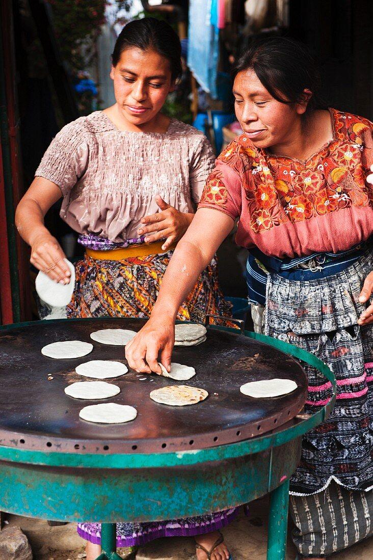 Mayan women baking tortillas at the market in Santiago Sacatepequez, Guatemala, Central America