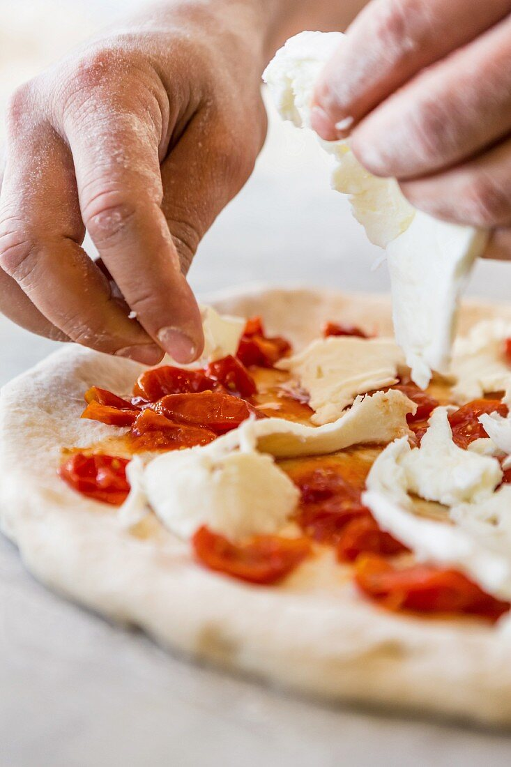 Mozzarella being placed on top of a pizza
