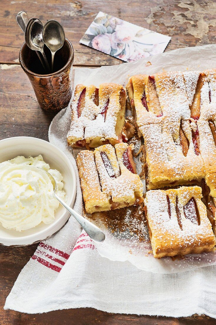 Plum and cardamom cake with icing sugar and cream