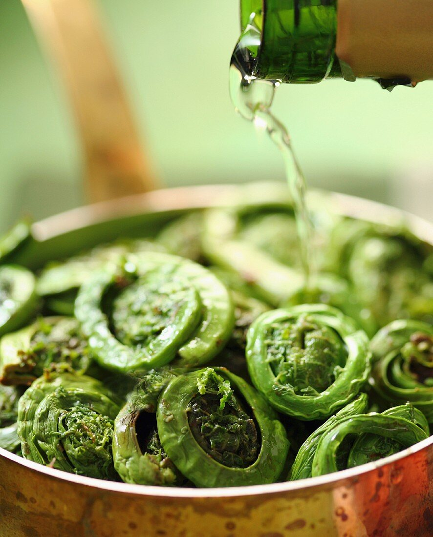 Wine being poured over fiddleheads