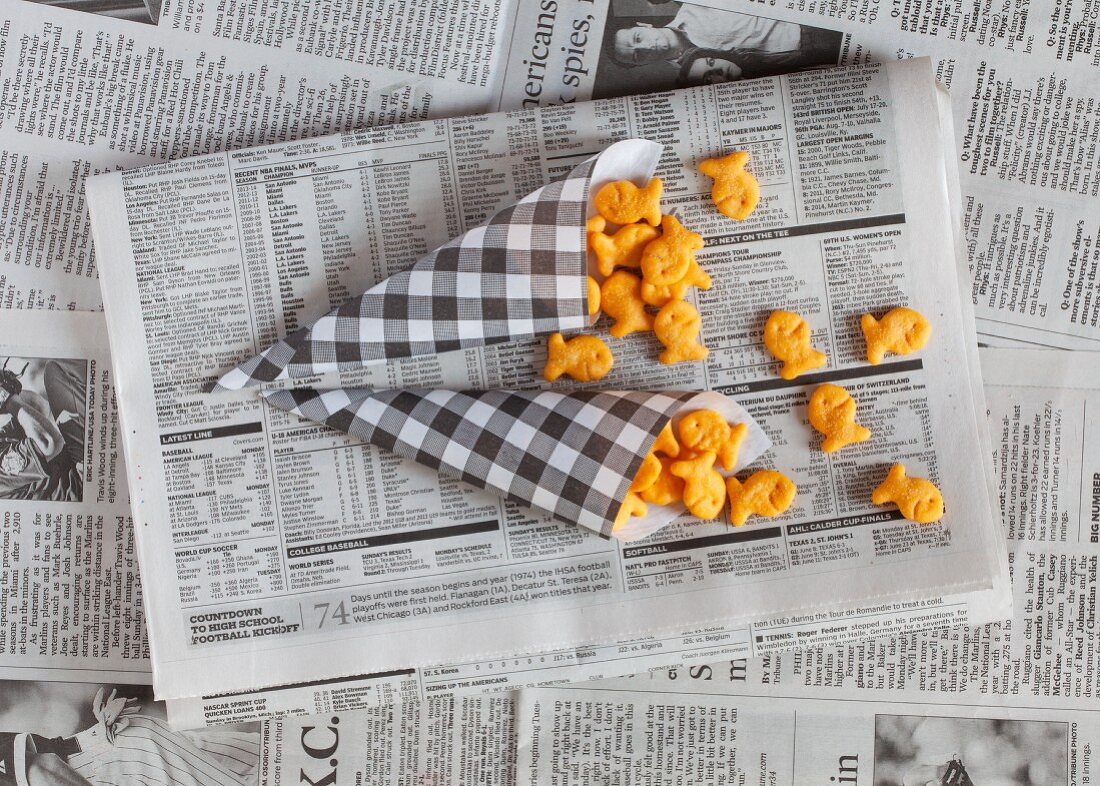 Fish shaped crackers in paper cones on a piece of newspaper