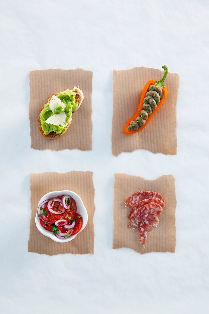 Mushy pea crostino, a pepper with anchovy cream, tomato salad with red onions and salami