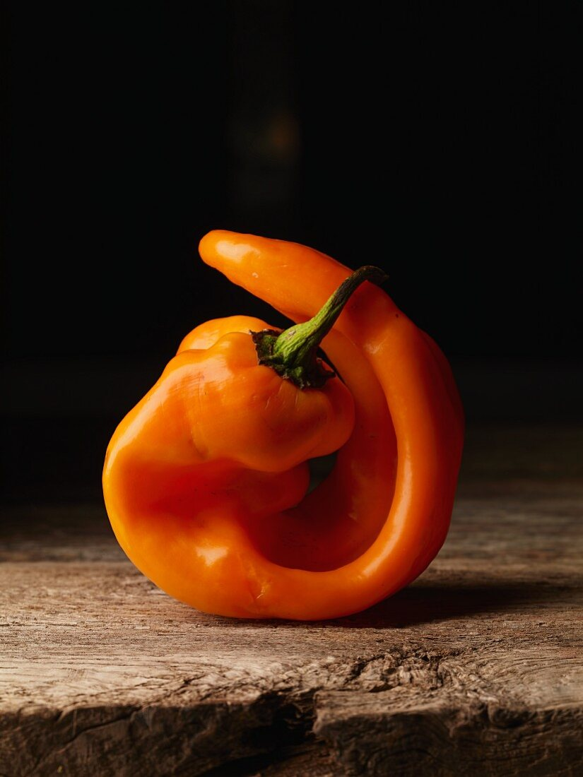 An orange pepper on a rustic wooden surface