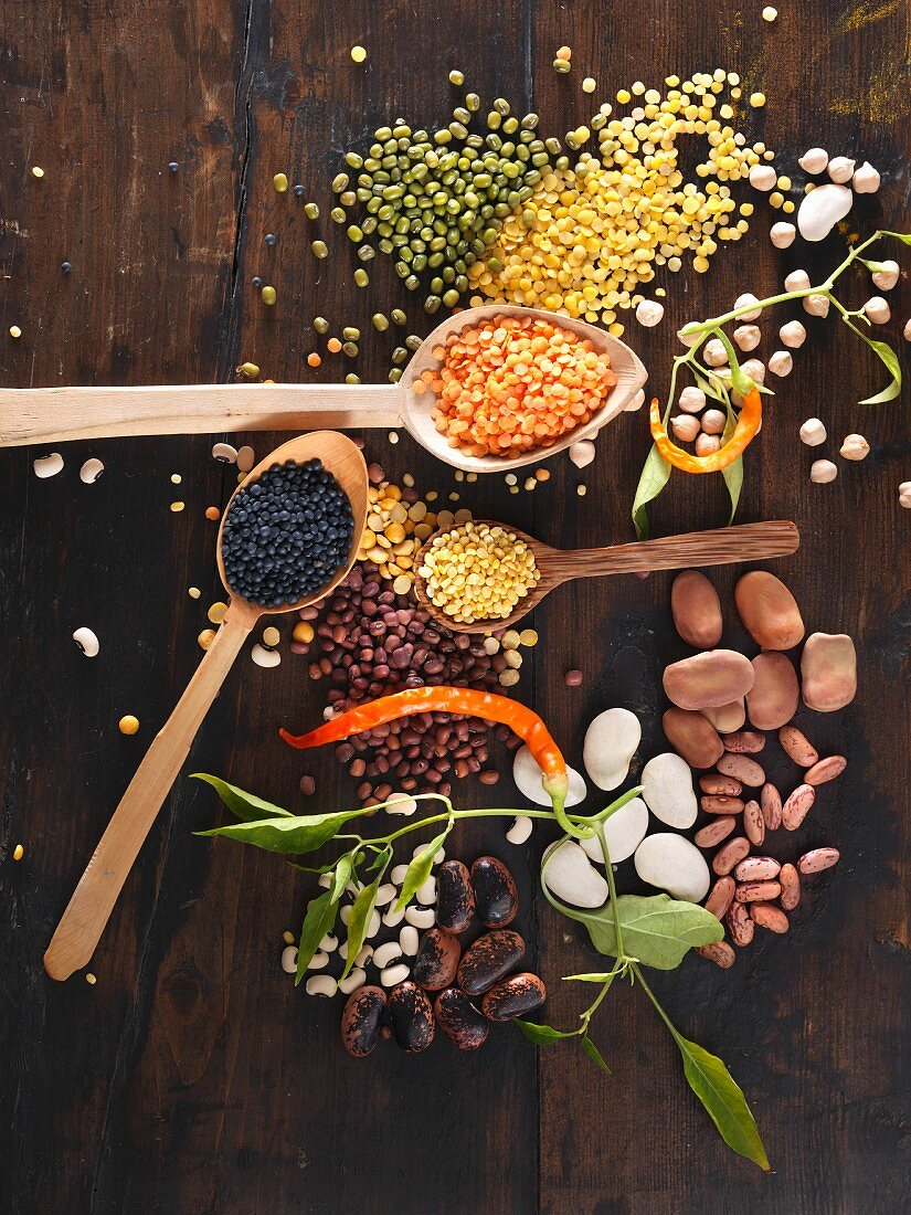 Various legumes on wooden spoons