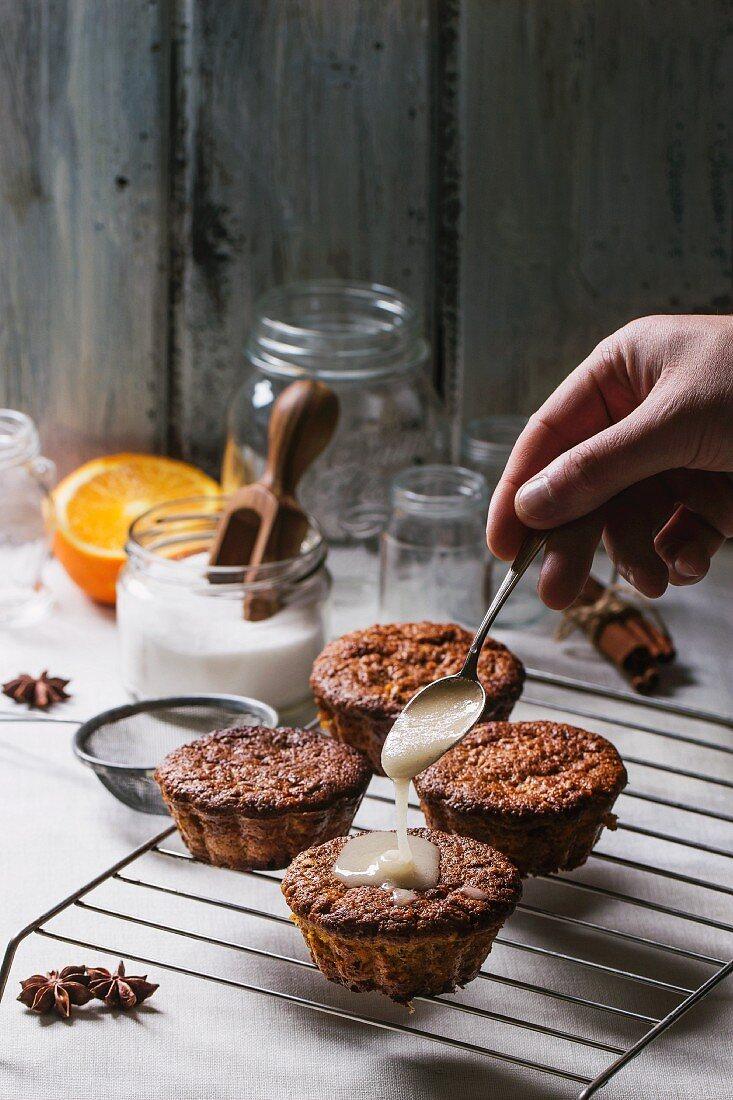 Mini orange cakes being drizzled with glaze